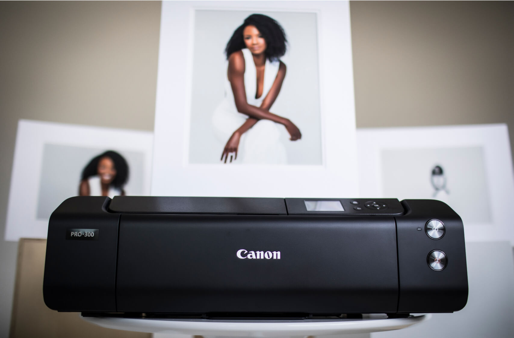 Canon imagePROGRAF PRO-300 with matted prints behind it