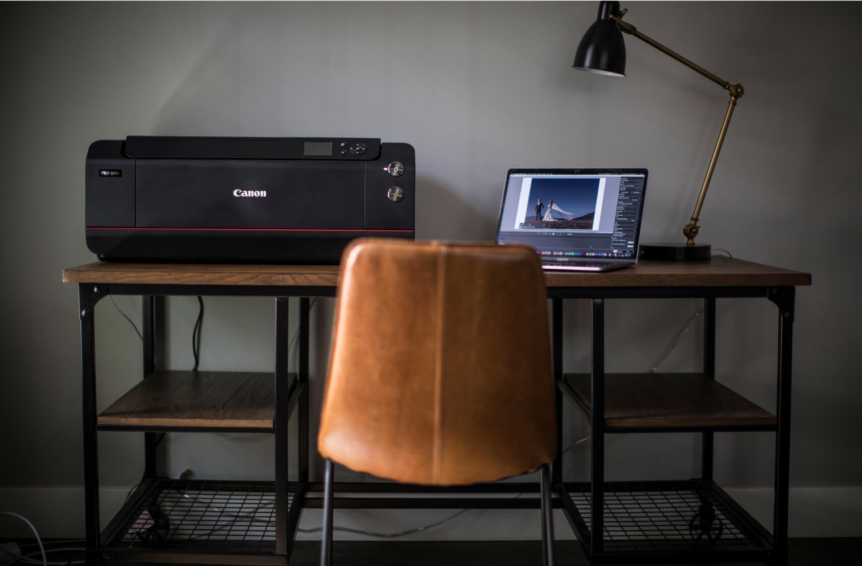 Pulled back shot of Canon Printer and laptop on a desk